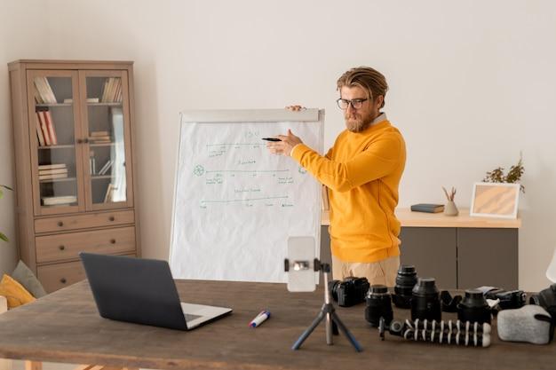 Współczesny młody nauczyciel z zakreślaczem stoi przy tablicy przed laptopem i aparatem w smartfonie podczas objaśniania