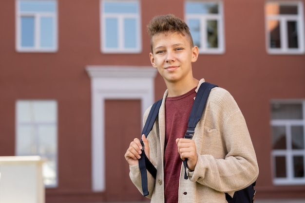Współczesny młodzieniec z plecakiem stojącym na zewnątrz budynku
