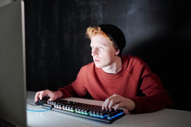 Współczesny nastolatek w bluzie i czarnej czapce naciskając klawisze na klawiaturze i klikając myszką siedząc przed ekranem komputera