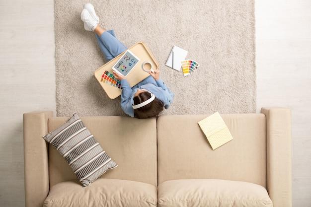 Współczesny projektant w niebieskiej piżamie siedzi na podłodze przy kanapie, słucha muzyki, pije kawę i wybiera kolory dla nowego logo