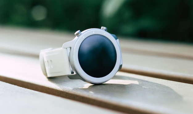 Współczesny smartwatch. zbliżenie na cpnteporny, stylowy, biały smartwatch, który leży na drewnianej ławce.