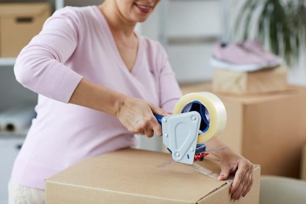 Współczesny sprzedawca opakowań do pakowania towarów online z taśmą klejącą