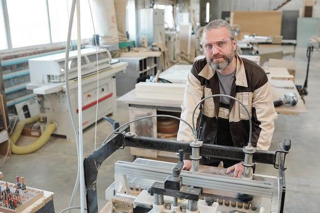 Współczesny starszy pracownik fabryki patrzy na ciebie podczas pochylania się nad maszyną do obróbki drewna na tle wnętrza warsztatu