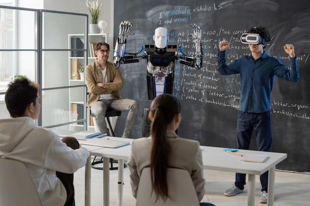 Współczesny student z zestawem słuchawkowym vr, demonstrujący umiejętności robota automatyki przed kolegami z klasy podczas prezentacji