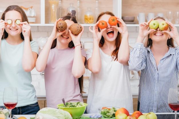 Wspólna dieta. zdrowe odżywianie. gotowanie ekologiczne. podekscytowane młode kobiety pozują z jedzeniem zakrywającym oczy.