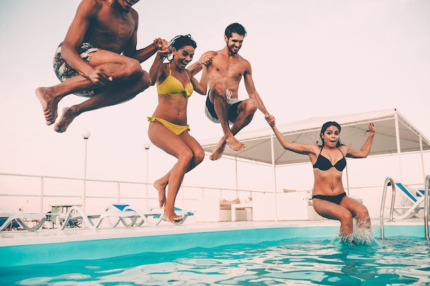 Wspólna impreza przy basenie. grupa pięknych młodych ludzi wyglądających na szczęśliwych podczas wspólnego skakania do basenu