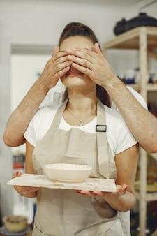 Wspólna praca twórcza. młoda para piękny w ubranie i fartuchy. ludzie trzymają naczynia ceramiczne.