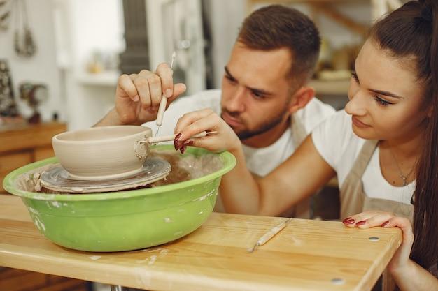 Wspólna praca twórcza. młoda para piękny w ubranie i fartuchy. ludzie tworzą miskę na kole garncarskim w glinianej pracowni.
