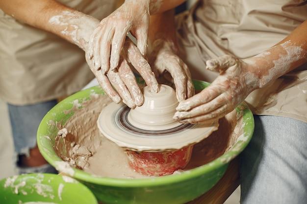 Wspólna praca twórcza. ręce tworząc miskę na kole garncarskim w glinianej pracowni.