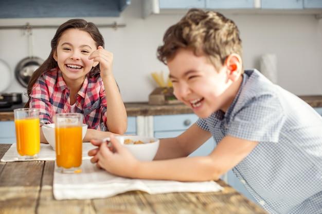 Wspólna zabawa. całkiem radosna ciemnowłosa dziewczynka śmiejąca się i jedząca śniadanie z bratem i bratem też się uśmiechającym