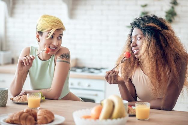 Wspólna zabawa. dwie wesołe młode dziewczyny w zwykłych ciuchach w figlarnym nastroju jedzące śniadanie z widelcami z pomidorami
