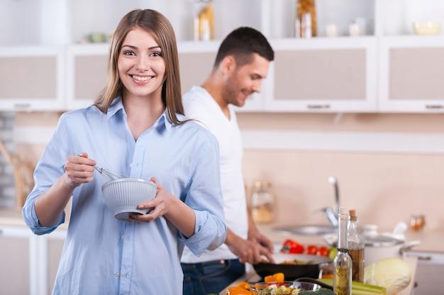 Wspólne gotowanie śniadania. szczęśliwa para gotuje razem w kuchni, podczas gdy kobieta patrzy na kamerę i uśmiecha się