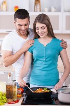 Wspólne gotowanie to świetna zabawa. szczęśliwa młoda para gotuje razem w kuchni