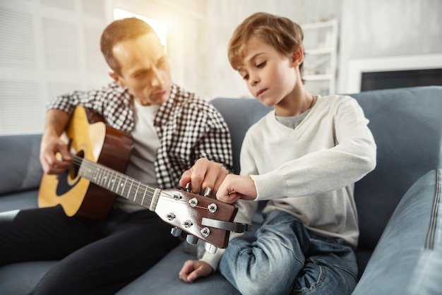 Wspólne granie. atrakcyjny radosny dobrze zbudowany mężczyzna trzymający gitarę i siedząc na kanapie uczy swojego syna gry na gitarze
