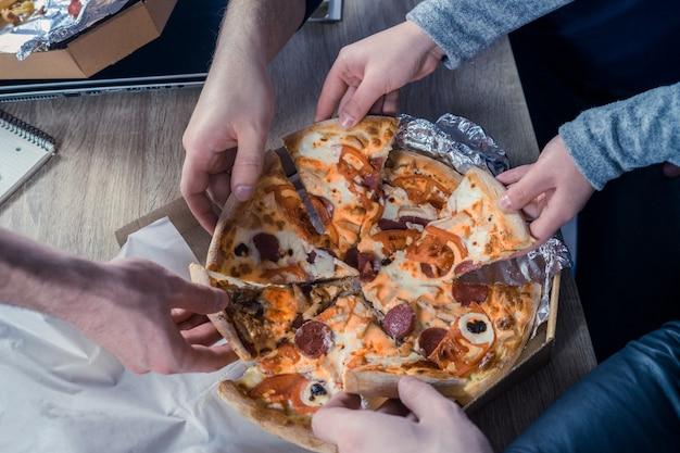 Wspólne jedzenie pizzy w biurze widok z góry na ręce biorące pizzę pojęcie przyjaźni