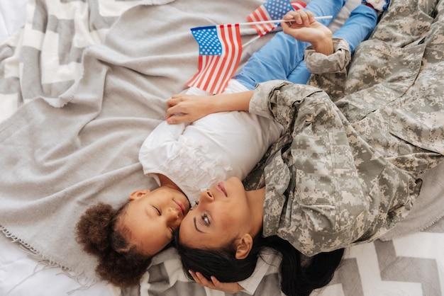 Wspólne marzenia. rozważna, silna młoda kobieta i jej córka wyglądają spokojnie, zdrzemną się po zaplanowaniu wakacji mam w domu