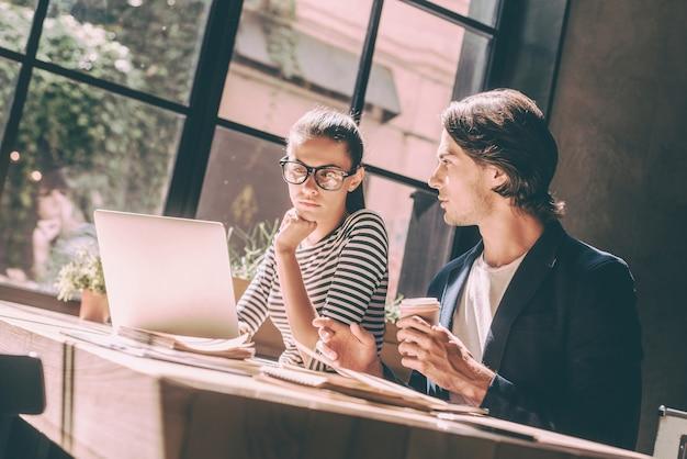 Wspólne omawianie nowego projektu. pewny siebie młody mężczyzna i kobieta pracując razem siedząc przy drewnianym biurku w kreatywnym biurze lub kawiarni