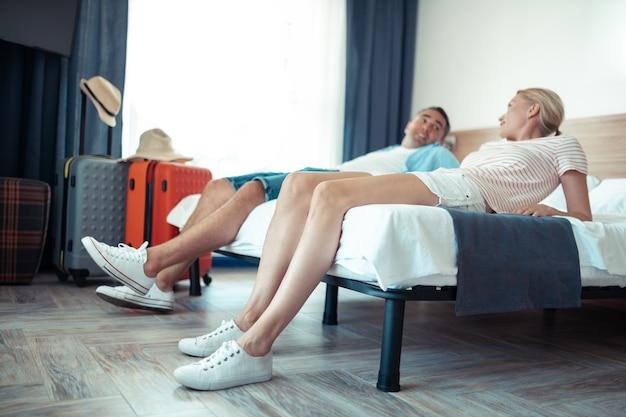 Wspólne planowanie. szczęśliwa para małżeńska robi plany na wakacje r. razem na łóżku hotelowym.