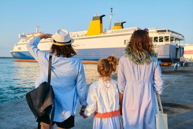 Wspólne rodzinne wakacje, mama i dwie córki w porcie morskim w pobliżu promu, wakacje, transport morski