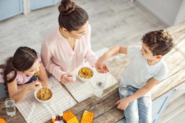 Wspólne śniadanie. sportowa ciemnowłosa młoda matka uśmiecha się i daje witaminy swojemu synowi siedzącemu na stole i córce jedzącej śniadanie