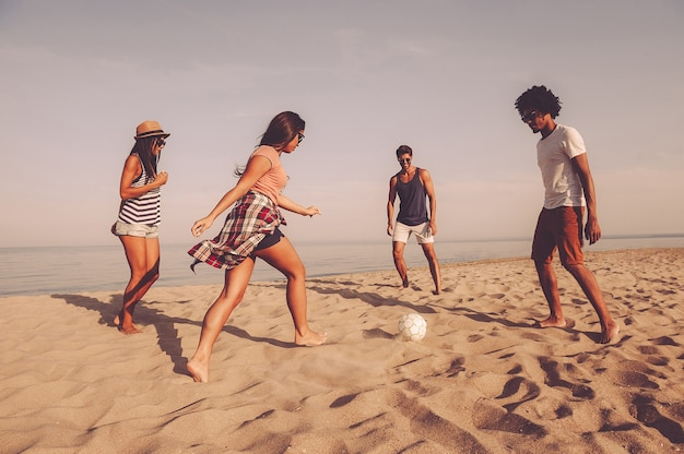 Wspólne spędzanie beztroskiego czasu. grupa wesołych młodych ludzi bawiących się piłką nożną na plaży z morzem w tle