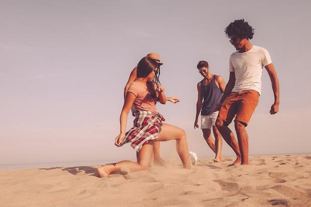 Wspólne spędzanie czasu na plaży. grupa wesołych młodych ludzi bawiących się piłką nożną na plaży