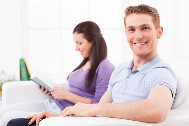Wspólne spędzanie czasu wolnego. wesoły młody mężczyzna patrzący w kamerę i uśmiechający się, podczas gdy kobieta siedzi za nim na kanapie i czyta książkę