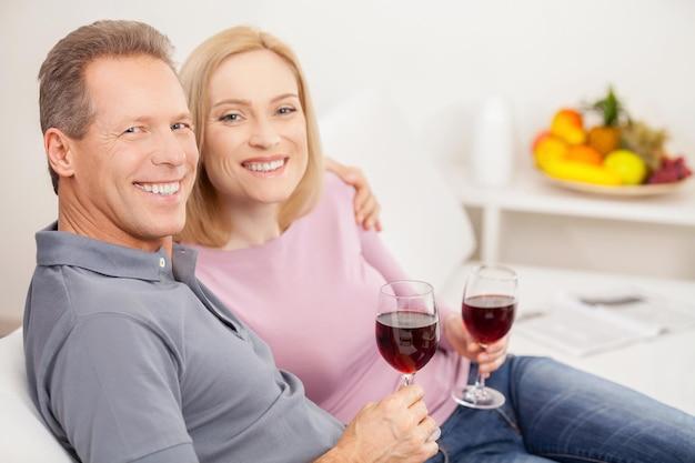 Wspólne spędzanie wolnego czasu. widok z boku na uśmiechniętą dojrzałą parę siedzącą razem i trzymającą kieliszki z czerwonym winem