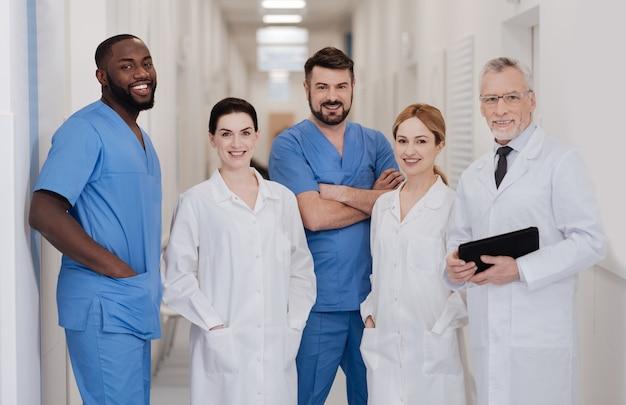 Wspólne studia nowych. uśmiechnięci profesjonalni pozytywni lekarze, którzy czerpią przyjemność z pracy w szpitalu i pracują w jednym zespole, jednocześnie wyrażając pozytywne nastawienie