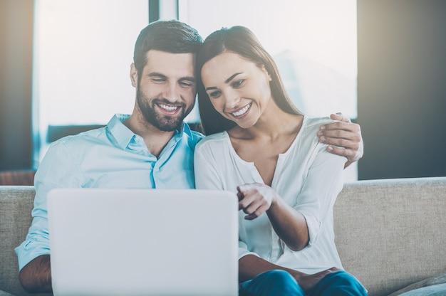 Wspólne surfowanie po sieci. piękna młoda kochająca się para siedzi razem na kanapie i patrzy na laptopa