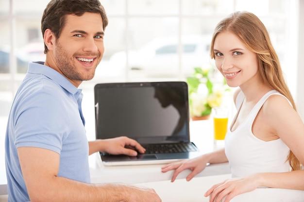 Wspólne surfowanie po sieci. przystojny młody mężczyzna siedzi przy stole i korzysta z laptopa, podczas gdy jego dziewczyna stoi za nim