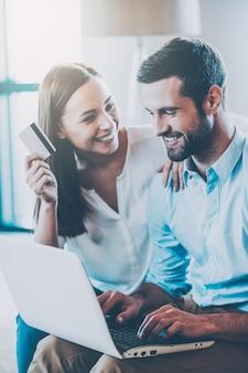 Wspólne zakupy online. piękna młoda kochająca para robi zakupy razem online, podczas gdy kobieta trzyma kartę kredytową i uśmiecha się