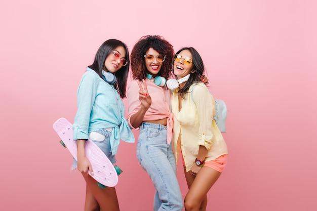 Wspólny portret trzech międzynarodowych koleżanek śmiejących się razem. wewnątrz zdjęcie ładnej skaterki spędzającej czas z uroczymi stylowymi damami.