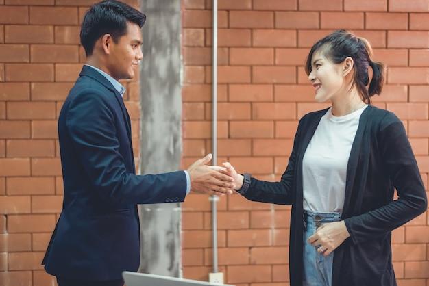 Współpraca biznesowa: pewni ludzie biznesu, ściskając ręce w biurze.
