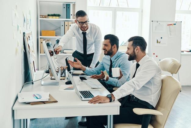 Współpraca w działaniu. grupa młodych, nowoczesnych mężczyzn w strojach formalnych, pracujących przy komputerach, siedząc w biurze