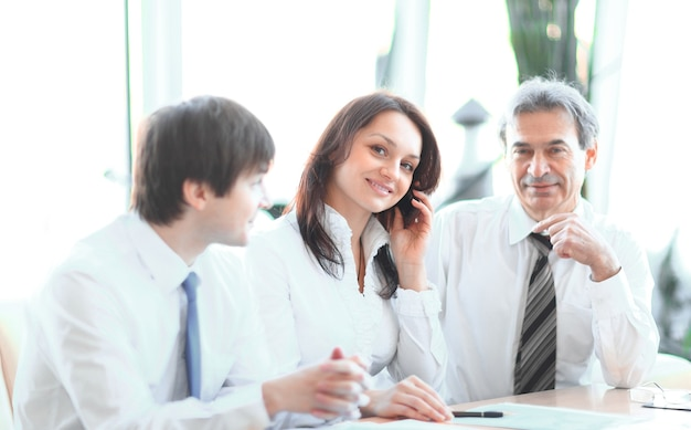 Współpracownicy analizujący statystyki finansowe siedzący przy biurku w biurze.