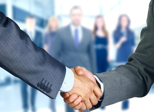 Współpracownicy biznesowi podają sobie ręce w biurze