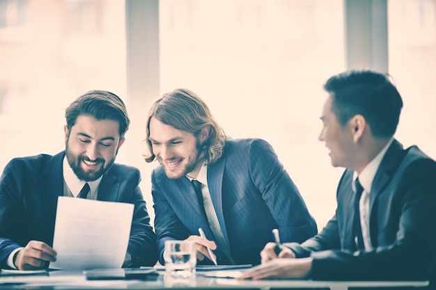 Współpracownicy czytanie dokumentu i śmieje