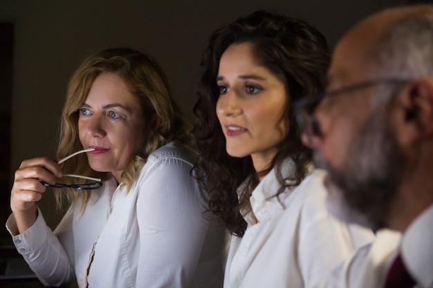 Współpracownicy dyskutuje projekt w biurze przy nocą