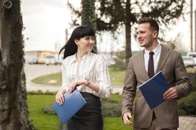 Współpracownicy idą razem i uśmiechają się