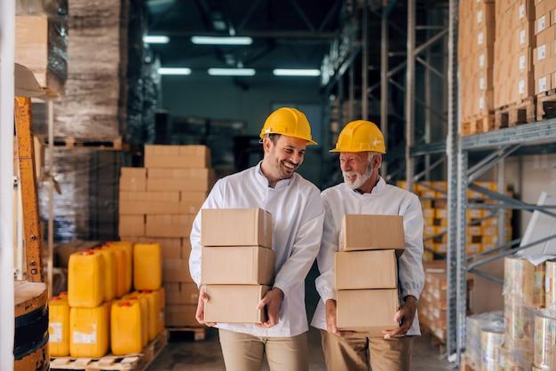 Współpracownicy niosący pudełka z hełmami na głowach. wnętrze do przechowywania.