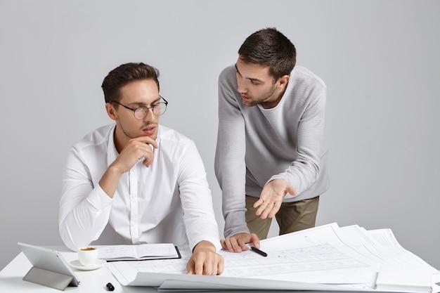 Współpracownicy płci męskiej robią papierkową robotę