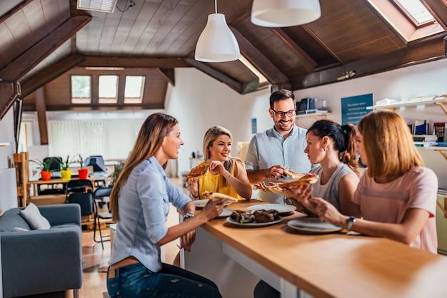 Współpracownicy początkującej firmy w przerwie obiadowej w nowoczesnym środowisku.