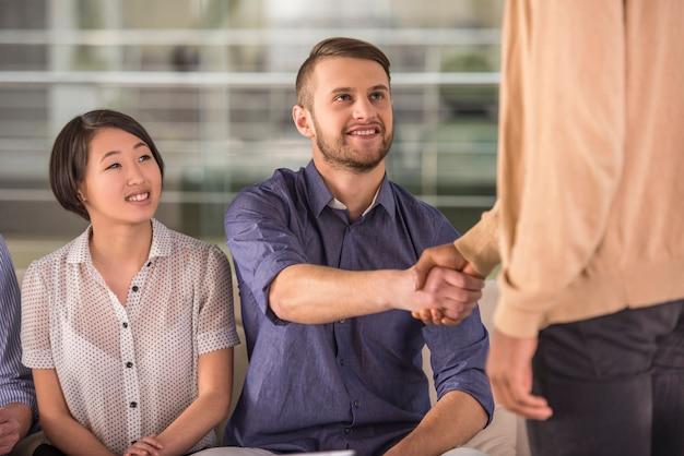 Współpracownicy podają sobie ręce podczas spotkania w biurze.