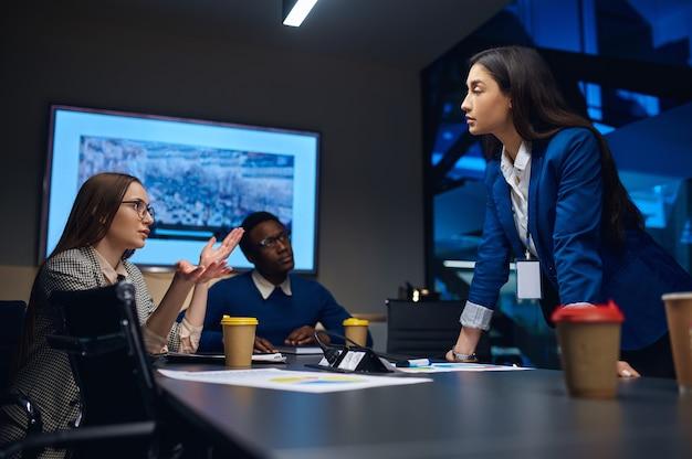 Współpracownicy podczas negocjacji biznesowych w biurze nocnym. senni menadżerowie i menadżerowie, ciemne wnętrze centrum biznesowego, nowoczesne miejsce pracy