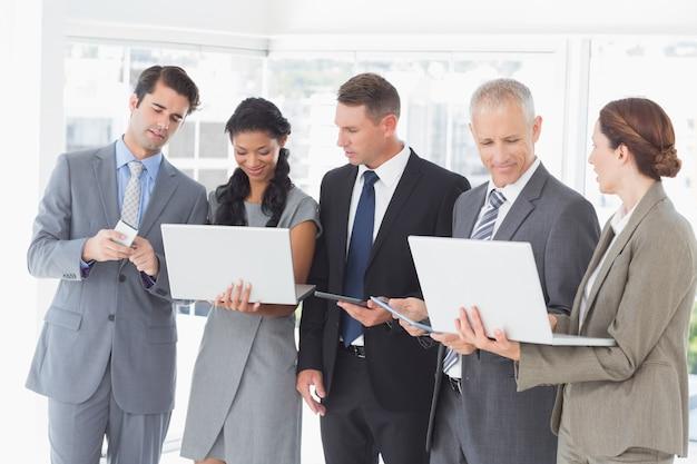 Współpracownicy pokazujący swoje urządzenia multimedialne dla siebie