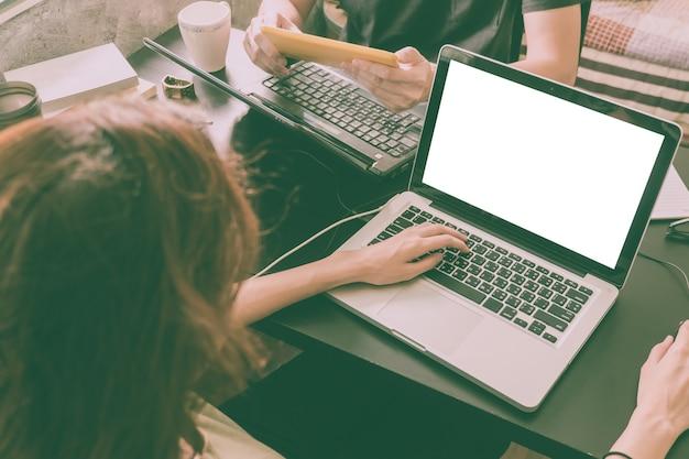 Współpracownicy pracujący na tym samym biurku, używają laptopa z pustym ekranem, uruchom bu