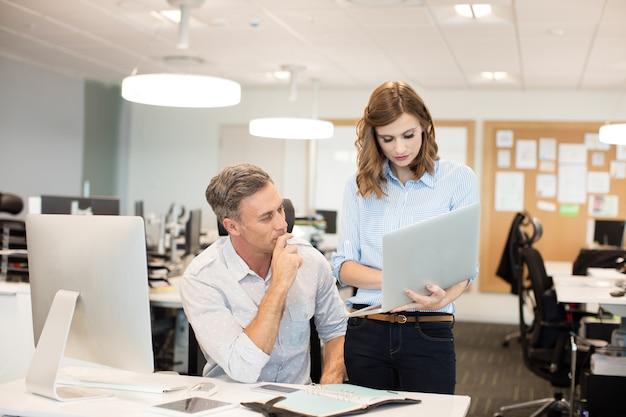 Współpracownicy pracujący razem na laptopie przy biurku