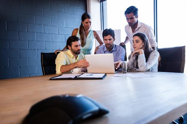 Współpracownicy pracujący razem na laptopie