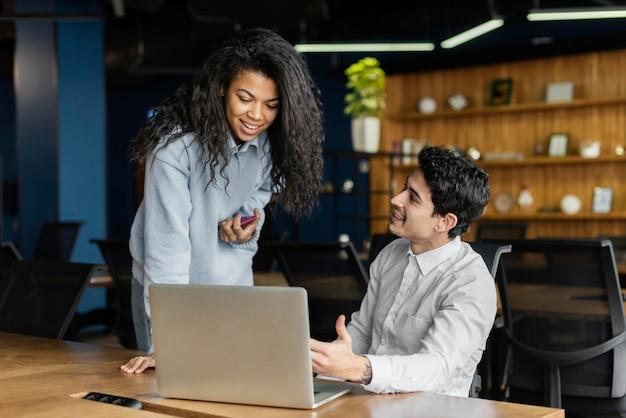 Współpracownicy pracujący razem w biurze z laptopem